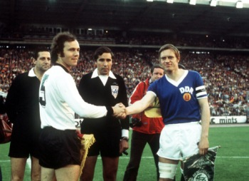 West Germany captain Franz Beckenbauer  shakes hands with East Germany captain Bernd Bransch before the match